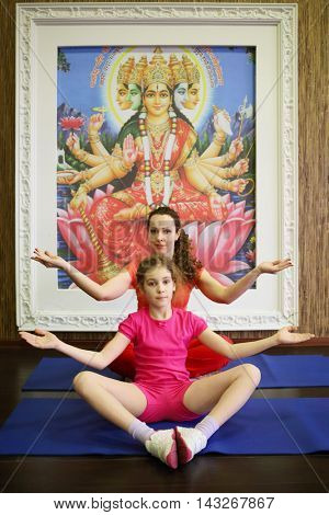 MOSCOW - APR 20, 2015: Woman and girl (with model releases) do  exercise of yoga in fitness club Zebra on Preobrazhenskaya Subway station