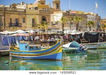 Malta - Marsaxlokk market with traditional Luzzu fishing boats on a beautiful summer day withblue sky and green sea
