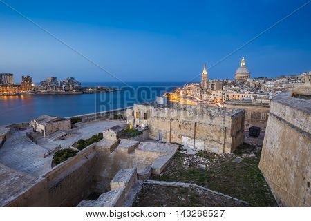 Valletta, Malta - Ancient walls of Valletta and St.Paul's Anglican Cathedral and houses of Sliema at blue hour
