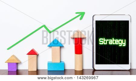 Strategy Business success growing concept on tablet. Toy block rise with Strategy planning stepping up diagram graph. Tablet with hi tech tech text Business strategy success rising up.