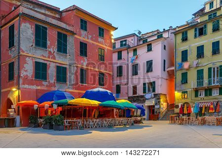 Night fishing village Vernazza with colorful umbrellas and tables on town square, Five lands, Cinque Terre National Park, Liguria, Italy.