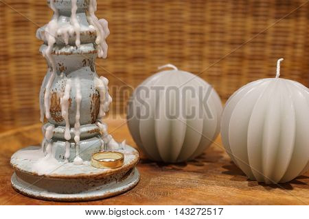 One gold wedding ring beside a candlestick