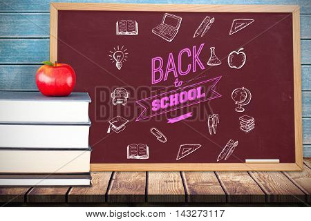 Back to school message with icons against composite image of black board Composite image of black board against wooden planks
