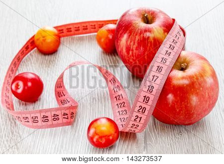 Red beautiful apples and plums meter ribbon on a wooden background