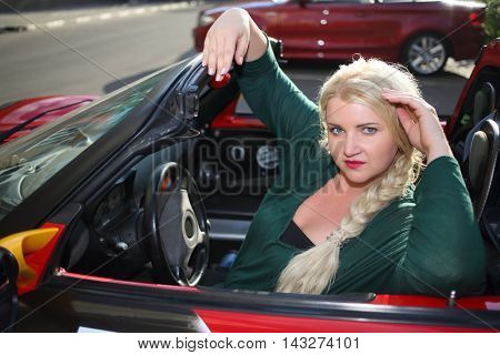 Blonde young woman poses in red sport car at summer sunny day