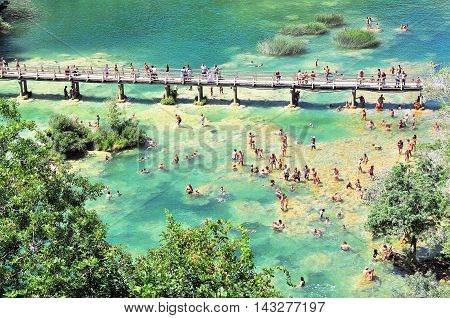 Green lake of Krka national park. Top view of the wooden bridge and the swimming people