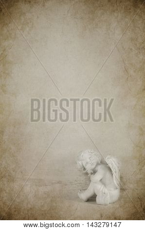 Angel figurine on a old wooden grunge background for mourning items.