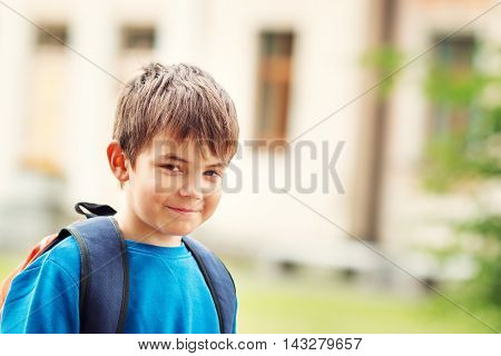 Boy with rucksack infront of a school building. Child with a backpack