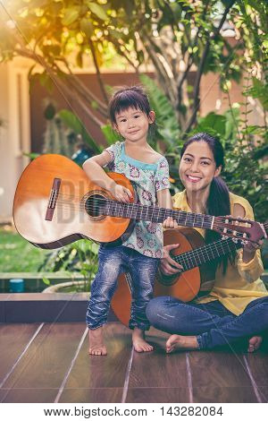 Mother With Daughter Play Guitar. Family Spending Time Together At Home. Vintage Style.