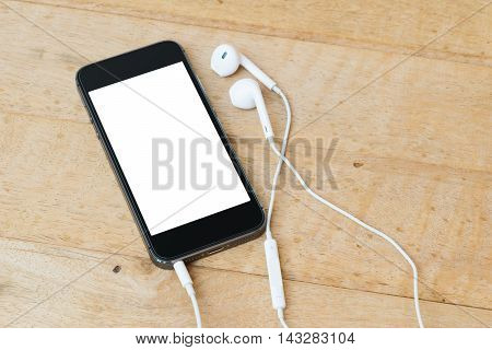 black mobile phone with Earphone on wood background