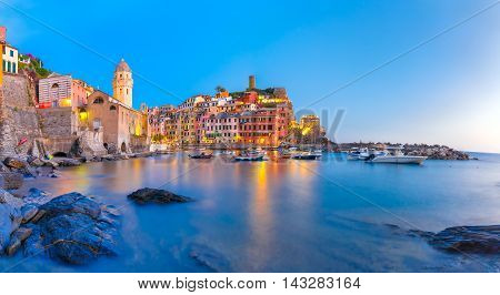 Panorama of night fishing village Vernazza with Santa Margherita di Antiochia Church and lookout tower of Doria Castle, Five lands, Cinque Terre National Park, Liguria, Italy.