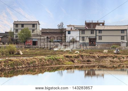 Heqing China - March 16 2016: Farmers working in the fields in Heqing in Yunnan