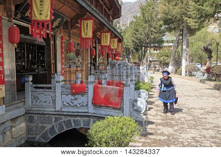 Heqing, China - March 16, 2016: Old Bayi Woman Walking In The Center Of Heqing Village.