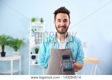 Happy man holding bank terminal in shop