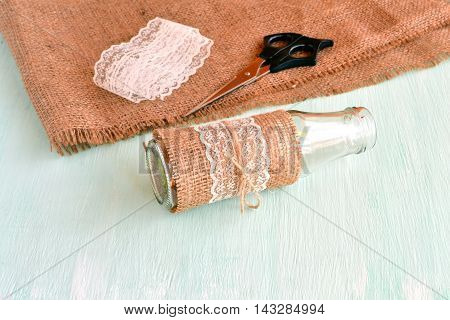 Handmade empty vase, scissors, burlap, lace. Set for handmade vase. Simple and cheap decorating glass bottles. Home decor project