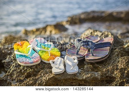 Three family flip-flops at the beach of Valletta, Malta - Mother's, Father's and baby's flip-flops in the sunset