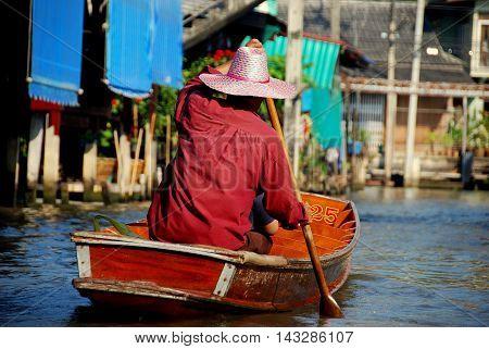 Damnoen Saduak Thailand - January 9 2010: Boatman paddles his tourist boat along a canal at the Damnoen Saduak Floating Market *