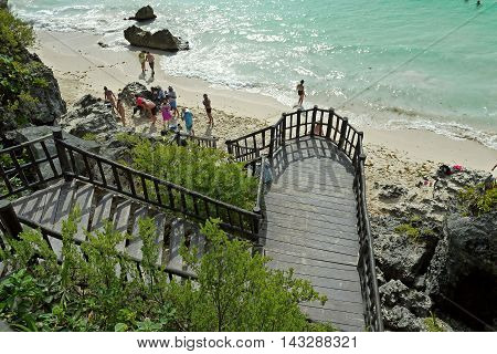 TULUM, MEXICO - AUGUST 26, 2014: Idyllic beach of Tulum with people swiming in caribbean sea. Tulum is an archaeological site in the Riviera Maya, Yucatan.