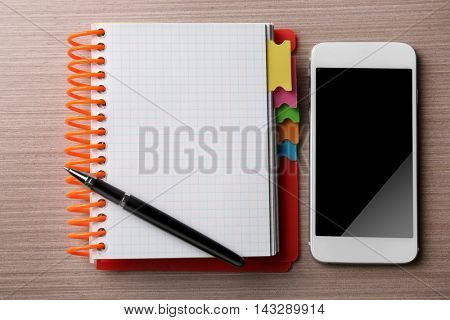 Notepad, pen and phone on wooden background