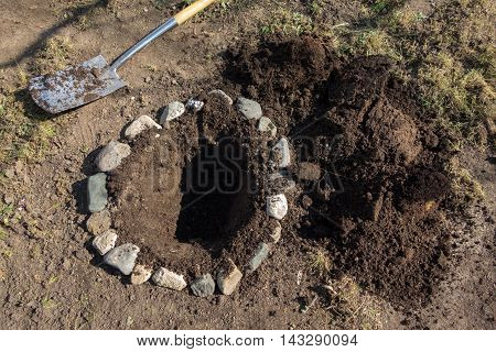 Hole surrounded of stones ready for planting tree