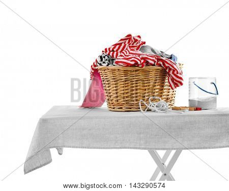Wicker basket with baby laundry and washing powder on white background