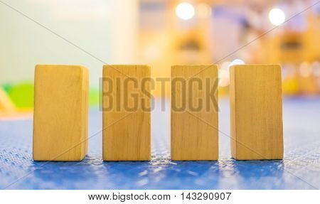 Children wooden Toy block arrange facing the camera. The space on wooden Toy block can be use for text. Four Toy block standing up on a rubber floor.