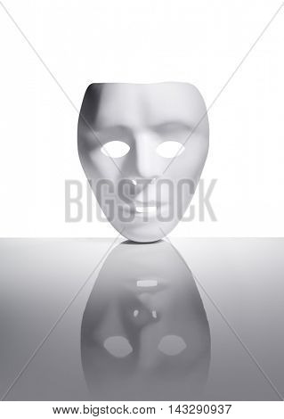 White plastic mask on reflective surface.
