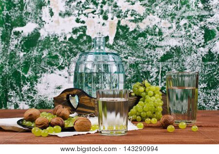Transparent drink made from grapes on a wooden background. Selective focus.