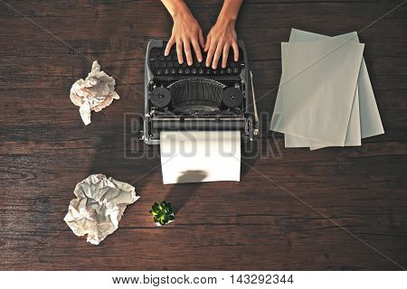 Woman hands working with retro typewriter and sheet of paper on wooden background