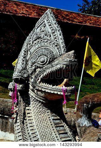 Lampang Thailand - December 28 2012: An immense Naga mythical dragon flanks the entry stairs to Wat Phra That Lampang Luan