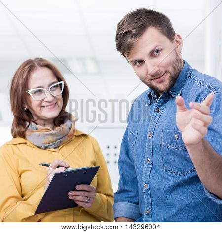 Young man with his experienced supervisor taking notes