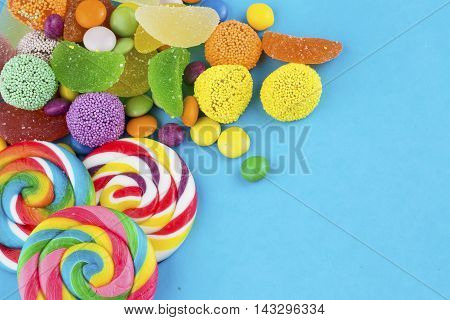 Colorful delicious mixed candies, on a blue background.