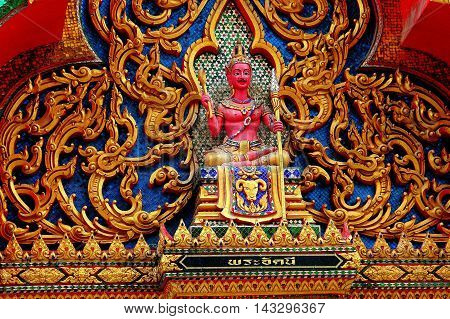 Nakhon Pathom Thailand - December 27 2005: Seated Buddha with pink face and torso on a temple tympanum at Wat Dai Lom
