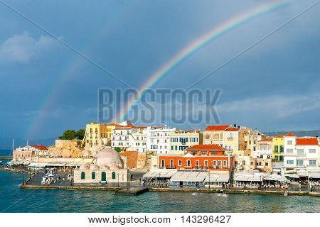 Scenic view of a rainbow after the rain of the Venetian waterfront of Chania. Mosque Hassan Kuchuk Pasha. Crete, Greece.