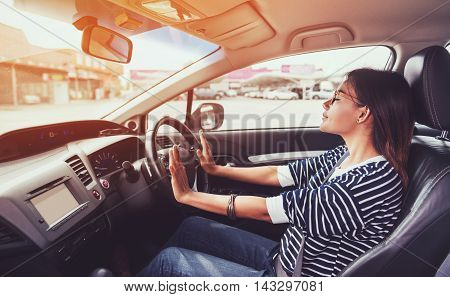 Asian woman driving a car in a happy moodfocus on hand
