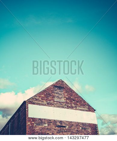 Blank Sign For Your Text On A Red Brick Industrial Building With Blue Sky And Copy Space