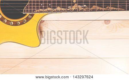 Half of Acoustic guitar on wooden floor in vintage tone.