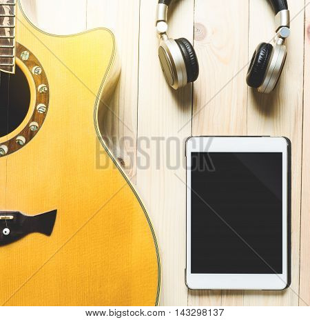 Acoustic Guitar with headphone and tablet for music practicing and music writing.
