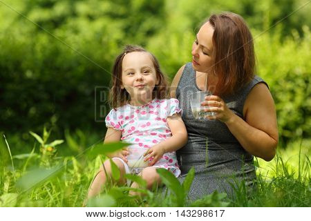 Little girl smiles and her mother with milk looks at she in sunny park