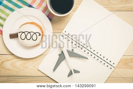 Travel planing in a colorful pastel cafe. Vacation planning book blank page with plane and donut. Planning your colorful vacation trip on a cafe table with coffee and donut.