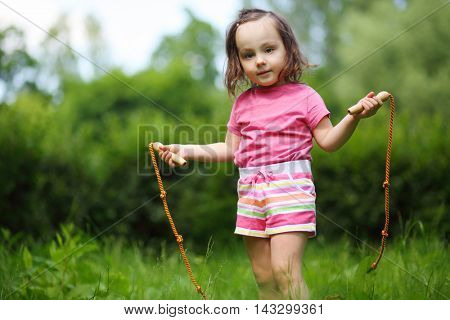 Little cute girl poses with skipping rope in summer sunny garden