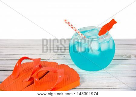 drink in fish bowl with orange flip-flops on whitewashed wood