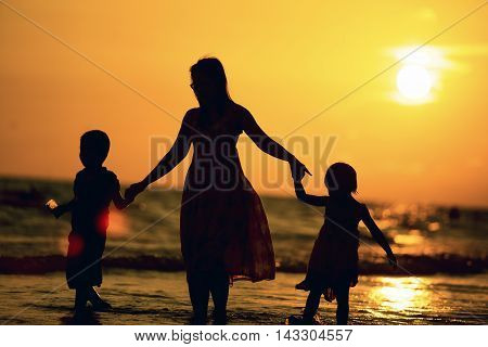 Mother and children walking along a beach on sunset