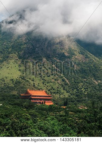 Chinese Buddhist monastery Po Lin on the mountain with clouds Hong Kong