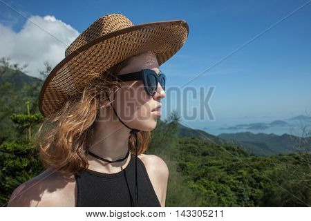 Young Blonde Female Traveler In Hat And Sunglasses At Sunny Summer Day On Mountains And Sea Backgrou