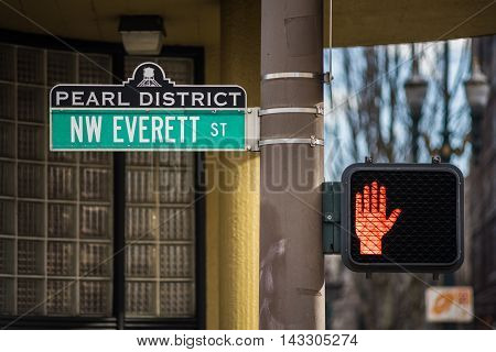 Sign of Pearl District in Oregon with Everett street and stop hand traffic light for pedestrians