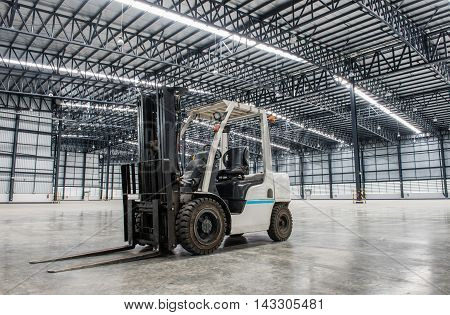 Forklift loader in large modern factory storehouse