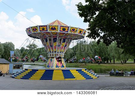 MUNICH GERMANY - 4 AUGUST 2015: Chains carousel in a fun fair on the grounds of the Olimpiapark near Olympia Tower.