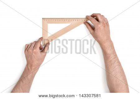 Man holding a wooden set square or right angle in the 90-60-30 conformation over a white background with copy space in a conceptual image , overhead view of his arms