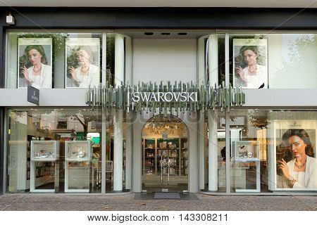 FRANKFURT AM MAIN GERMANY - AUGUST 6 2015: Swarovski store on Kalbacher Gasse street. The Swarovski Crystal range includes home decoration objects jewelry and couture and chandeliers.
